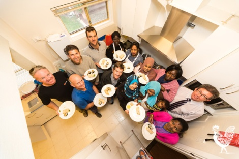 • Refugees and tradies show off their new kitchen. Photo by Jeremy Dixon