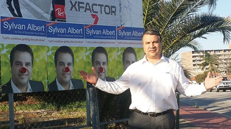 • Bayswater mayor Sylvan Albert, with some of his defaced posters, says this is the dirtiest election campaign he's been in. Photo supplied