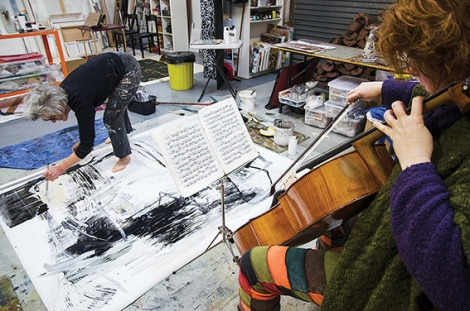 • Rachel Scott fiddles while Judith Wright paints. Photo supplied