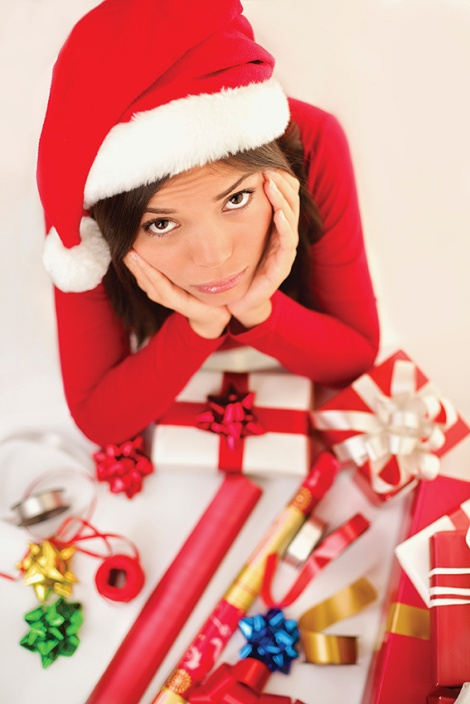 Sad christmas santa woman wrapping gifts depressed and bored wearing santa hat. Caucasian asian female model.