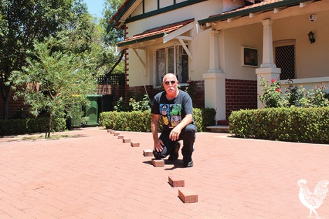 • Graeme Reany squats next to a line of bricks which show his new fence-line if the proposed widening of Guildford Road goes ahead.