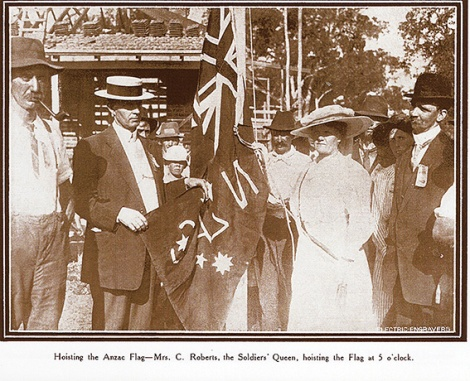 • Mrs C Roberts, the Soldiers' Queen, hoists the flag at Anzac Cottage.