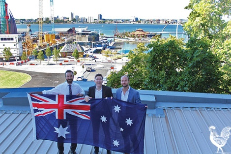 • Tim Hammond, Reece Harley, and Atlas building manager Steven Hasluck restoring the flag tradition at this 85-year-old building. Photo by Trilokesh Chanmugam